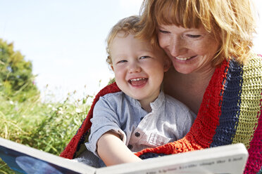 Happy mother and son with picture book in meadow - FSF00662