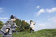 Three children playing in meadow - FSF00671