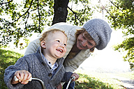 Happy mother with son on tricycle in the nature - FSF00680