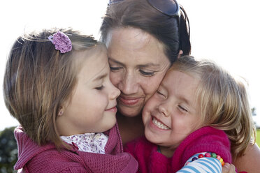 Mother hugging two girls outdoors - FSF00686