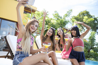 Young woman taking selfie with friends at the poolside - ABAF02140