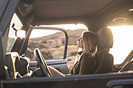 Woman sitting in car at sunset - SIPF01389