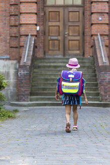 Back view of little girl with school bag in front of her school - JFEF00836