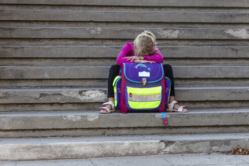 Sad little girl sitting on stairs with school bag - JFEF00839