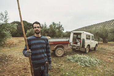 Spain, portrait of smiling worker with tool in olive grove - JASF01486