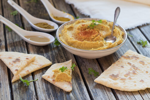 Bowl of Hummus and flat bread on wood - YFF00629