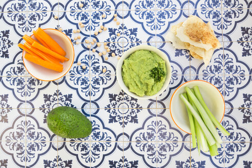 Bowls of avocado hummus and crudites, avocado, flat bread and chick-peas on tiles - LVF05825