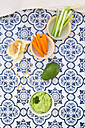 Bowls of avocado hummus and crudites, avocado, chick-peas and flat bread on tiles - LVF05828