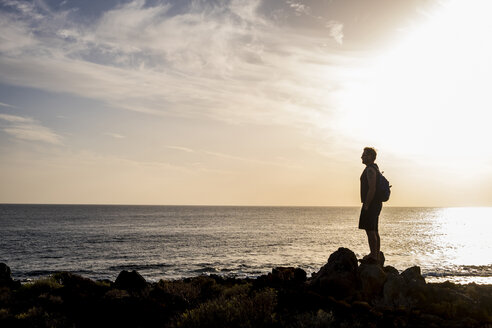 Spain, Tenerife, silhouette of man standing in front of the sea at sunset - SIPF01394