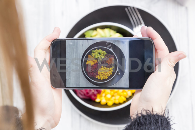Girl taking a photo of lunch bowl with her smartphone, close-up - SARF03150