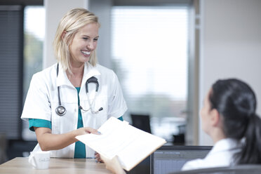 Doctor taking patient's record from receptionist - ZEF12610