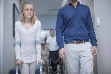 Girl with crutches walking with father in hospital - ZEF12628