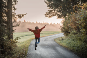 Back view of woman jumping with arms outstretched on country road in the evening - WVF00830