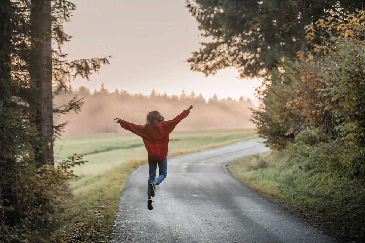 Back view of woman jumping with arms outstretched on country road in the evening - WVF00830 - Valentin Weinhäupl/Westend61