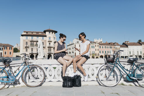 Italy, Padua, two young tourists sitting on railing looking at cell phones - ALBF00093