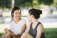 Two friends sitting in city park listening music together with earphones - ALBF00105