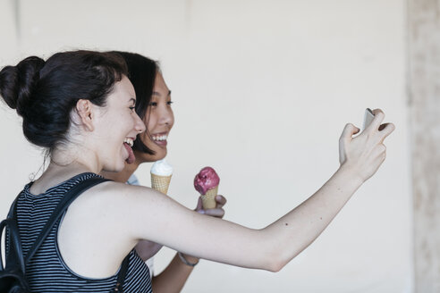 Two young women with ice cream cones taking selfie with smartphone - ALBF00117