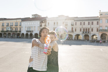 Italy, Padua, two young women with soap bubble machine - ALBF00120