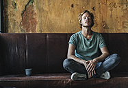Man sitting on couch in unfinished room - KNSF00885