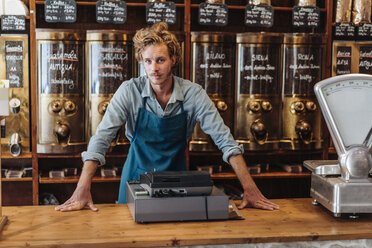 Portrait of coffee roaster at counter in his shop - KNSF00900