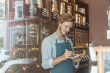 Coffee roaster taking notes in his shop - KNSF00912