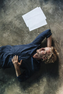 Man lying on floor next to papers - KNSF00918