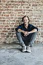 Smiling man sitting at brick wall - KNSF00924