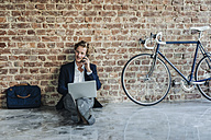 Businessman sitting on floor using laptop and cell phone - KNSF00930