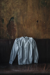 White shirt at couch in room with crumbling wall - KNSF00942