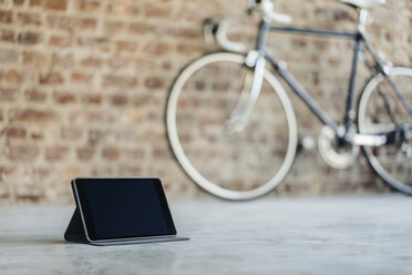 Tablet and bicycle in a room with brick wall - KNSF00963