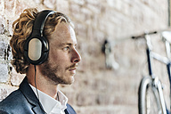 Businessman wearing headphones - KNSF00972