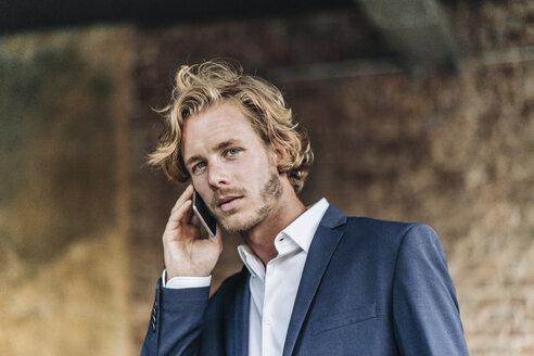 Confident businessman on cell phone - KNSF00978