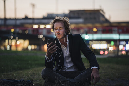 Businessman sitting on meadow at dusk with cell phone and earphones - KNSF00987