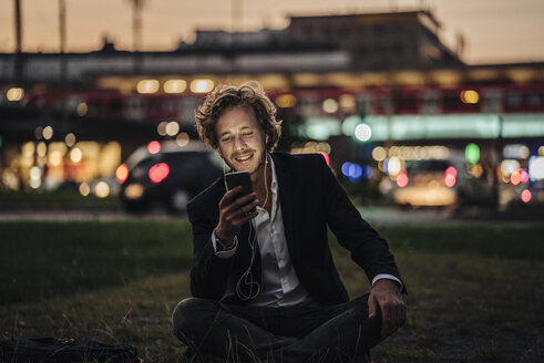 Smiling businessman sitting on meadow at dusk with cell phone and earphones - KNSF00990