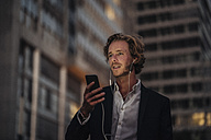 Businessman in the city at dusk using cell phone - KNSF00993