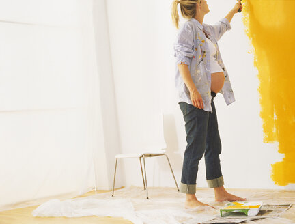 Pregnant woman paiting a wall - FSF00721