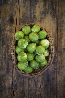 Wickerbasket of Brussels sprouts on dark wood - LVF05834