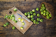 Brussels sprouts, kitchen knife and wooden board on dark wood - LVF05840
