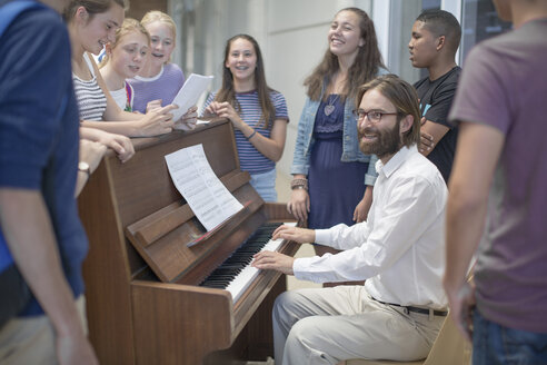Teacher with group of students standing around piano - ZEF12664