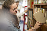 Female student at the library putting back book in book shelf - ZEF12667