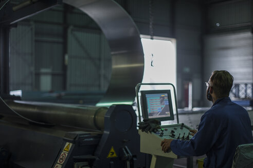 Worker operating machinery at control panel in steel factory - ZEF12678