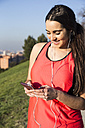 Smiling female athlete with earphones using her phone - ABZF01836