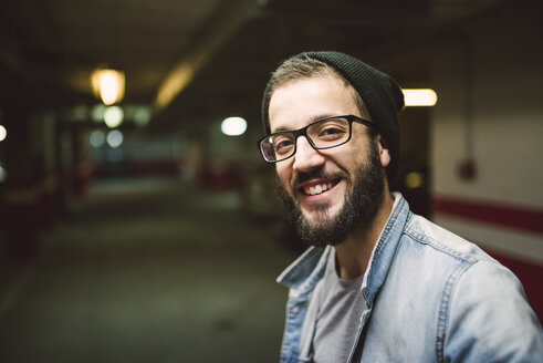 Portrait of smiling young man in a garage - RAEF01718