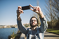 Smiling young man taking a selfie at the waterfront - RAEF01724