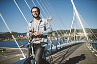 Smiling young man with fixie bike on a bridge - RAEF01727
