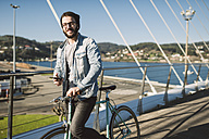 Smiling young man with fixie bike on a bridge - RAEF01730