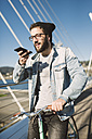 Young man with fixie bike on a bridge using smartphone - RAEF01733