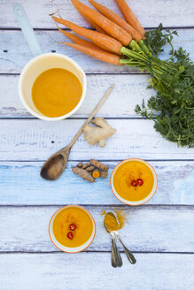 Saucepan and two bowls of carrot curcuma soup with ginger and chili - LVF05854