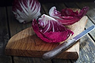 Leaves of radicchio and kitchen knife on wooden board - YFF00631