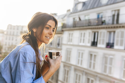 Young woman standing on balcony, holding cup of coffee - MGOF02868